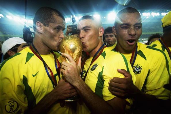 Ronaldo e Rivaldo baciano la coppa del Mondo appena vinta. Il Fenomeno con i capelli a mezzaluna, simbolo di quel mondiale