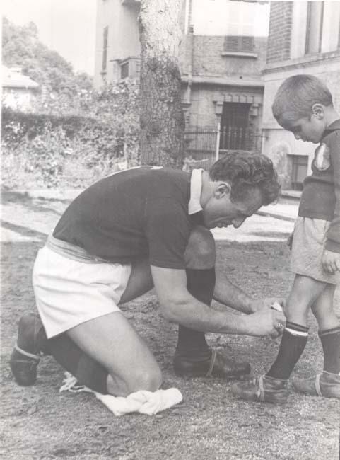 Valentino Mazzola mentre allaccia gli scarpini a un giovanissimo Sandro